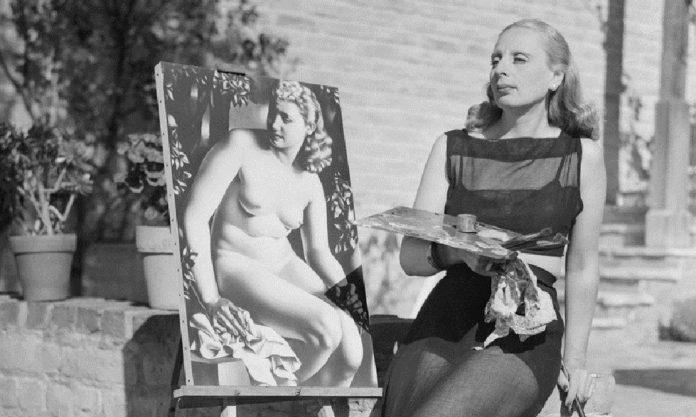 Tamara de Lempicka posa pintando frente a uno de sus cuadros Getty